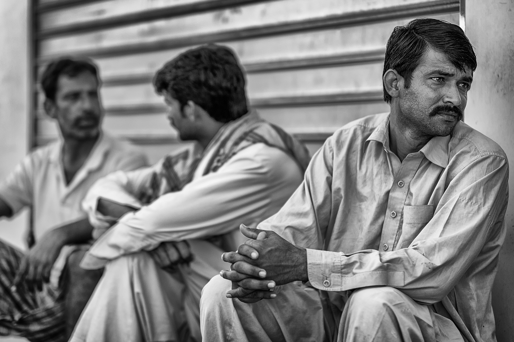 On Friday mornings, workers either wait in the street for a potential day job or enjoy their favorite cricket game.